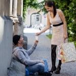 Woman gives a beggar money — Photo #8190136