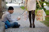 Beggars and rich woman with shopping bags — Photo