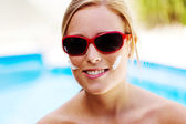 Woman with sunglasses and sun cream — Stock Photo
