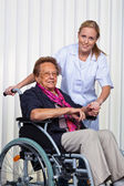 Nurse and the old woman in a wheelchair — Foto Stock