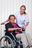 Enfermeira e a velha mulher em uma cadeira de rodas — Foto Stock