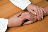 Hand of a nurse and an old senior citizen — Stock Photo