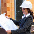 Architect with plan on construction site — Stock Photo