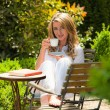 Woman drinking coffee in the garden — Stock Photo