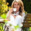 Woman drinking coffee at breakfast in the garden — Stockfoto