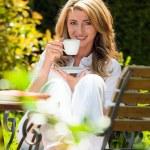 kobieta pije kawę w śniadanie w ogrodzie — Zdjęcie stockowe