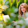 Stock Photo: Womwith laptop in garden