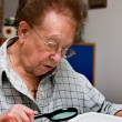 Elderly woman reads a book with glasses — Stock Photo