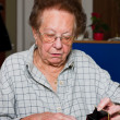 Stock Photo: Pensioner counts their money from pension