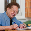 Senior writes a letter - Stock Photo