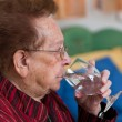 Elderly woman drinking water from a glass — Stock Photo