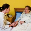 Sick old woman and nurse in a nursing home - Stock Photo