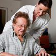 Nurses supervised old woman in a nursing home - Stock Photo