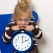 Foto Stock: Child with daylight saving time clock as symbol