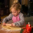 Child at christmas in advent when baking cookies - Stock Photo