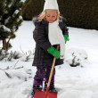 Shoveling snow in winter with snow shovel - Stock Photo