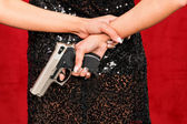 Woman in evening dress with concealed weapon — Stock Photo