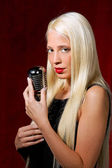 Young woman with a microphone as a singer — Stock Photo