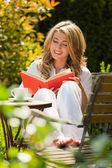 Woman reading a book in the garden — Stock Photo