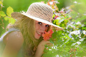 Woman smelling a rose in the garden — Stock Photo