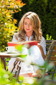 Woman reading the book in the garden — Stockfoto