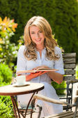 Woman reading a book in the garden — Stockfoto