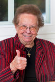 Successful elderly woman laughing with thumbs up — Stock Photo