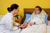 Sick old woman and nurse in a nursing home — Stock Photo