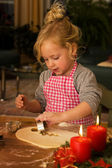 Child at christmas in advent when baking cookies — Stock Photo