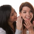 Two young women whispering to each other — Stock Photo