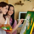 Young girl painting on an easel — Stock Photo