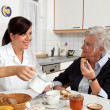 Nurse helps elderly woman at breakfast - Stock Photo