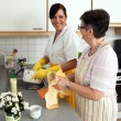 Nurse with elderly woman washing dishes - Stock fotografie