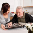 Stock Photo: Woman looks at a photo album with seniors