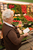 Senior shopping for food at the supermarket — Stock Photo