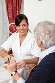Nurse helps elderly woman at breakfast — Stock Photo