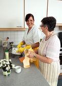 Nurse with elderly woman washing dishes — Stock Photo