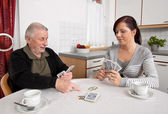 Woman playing with seniors in their free time with playing cards — Stock Photo