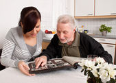 Woman looks at a photo album with seniors — Stock Photo