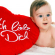Small child with a baby cushion i love you — Stock Photo #8282461