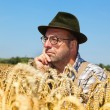 Thoughtful farmer in a corn field — Stock Photo