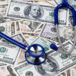 Stock Photo: Costs for health, stethoscope and dollar bills