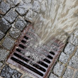 Lid of a channel for rain water — Stock Photo