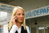 Blonde girl phone at the airport with the h — Stock Photo