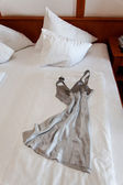 Nightgown on bed in hotel room — Stock Photo