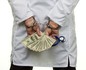 Doctor with dollar bills and handcuffs — Stock Photo
