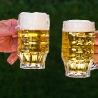 Two pitchers of beer with us beer foam - Stock Photo