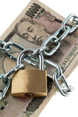 Japanese yen bank notes with lock and chain — Stock Photo