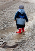 Child has fun with rainwear in the rain — Stock Photo