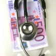 Stethoscope with pile of money — Stockfoto